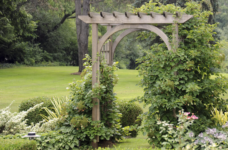 Simple wooden arbor with a pergola top.