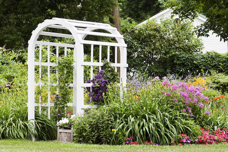 This classic white wooden arbor is tucked neatly into a lush garden  providing portal Backyard Arbor Designs and Ideas