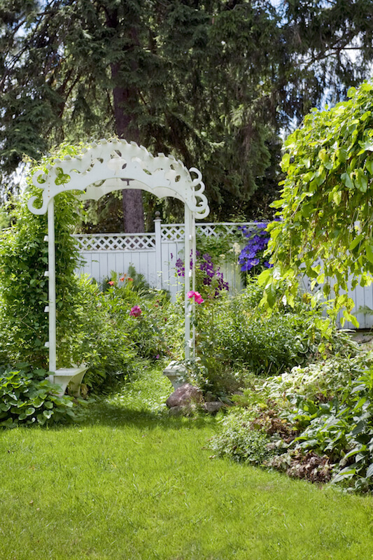 The incredibly ornate arbor has standard lattice sides, but the top has a decidedly more ornate, yet quaint, cottage feel.