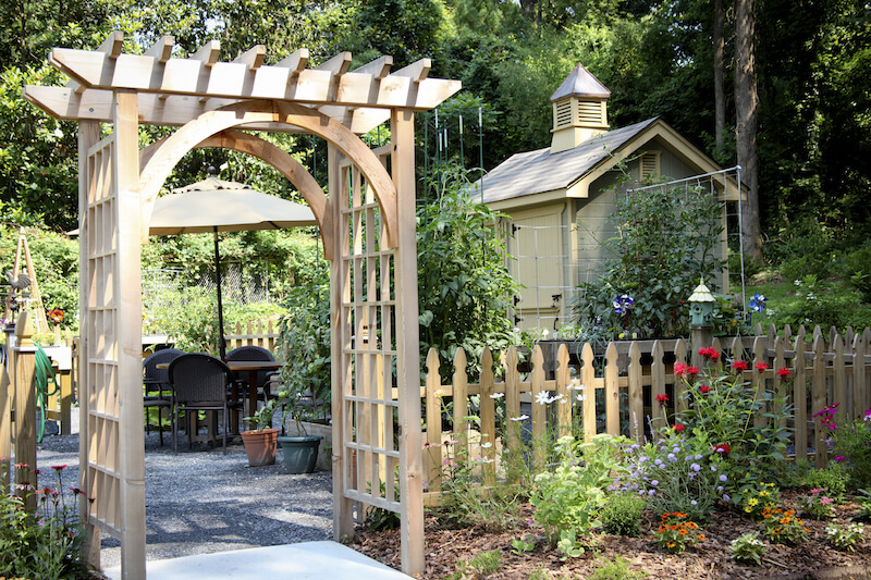 this simple wooden arbor rests at the entrance to a backyard patio to one side of - Arbor Design Ideas