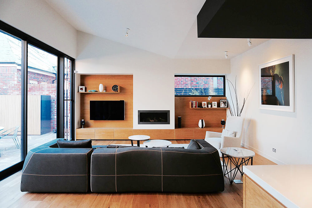 A stylish black sofa faces the fireplace in this living room with modular coffee table and built-in cabinet mounted with television and floating shelves.
