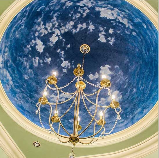 An elegant and sophisticated chandelier hangs from a bright dome with a design in this picture. With brighter colors in a dome, light can reflect the light that shines up back down into the room