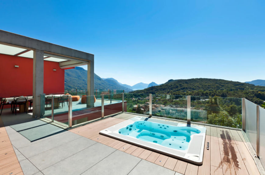 Frame-less glass railings are perfectly used to wall off a deck and hot tub area while still allowing guests to enjoy the incredible views.