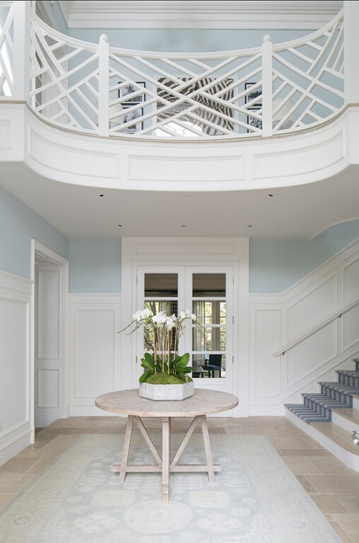 Even indoors, a Chippendale style railing adds incredible architecture and style to any home. This example works beautifully with the pale blue walls and white wainscoting.
