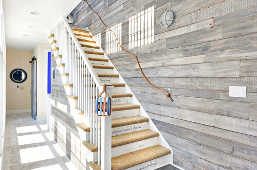 Sometimes, even just a simple sturdy rope attached to the stairwell can set a theme. Against the shiplap wall, it creates a nautical theme. Notice here that a sturdier handrail is provided on the other side.