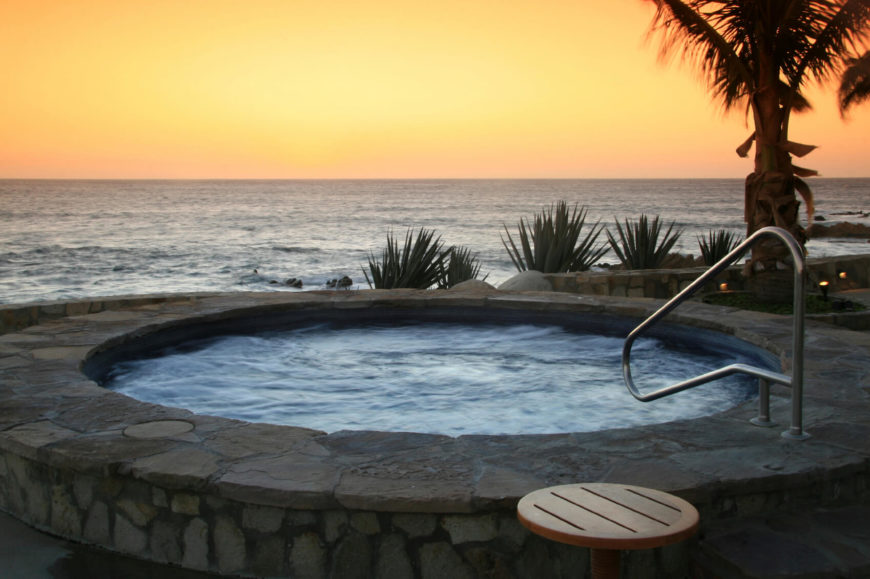 An in-ground hot tub looking out over the ocean at sunset.