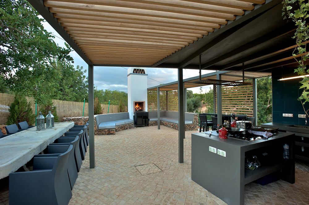 Large outdoor kitchen area featuring modish bar counter and a long dining table set. There's a sitting lounge near the fireplace as well.