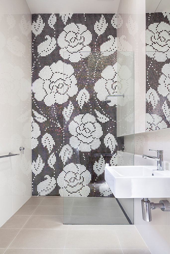 The bathroom is thoroughly modern, with a glass wrapped walk-in shower and large format tile flooring beneath sleek white walls. A flower pattern in the micro tile wall adds a dose of whimsy and art.