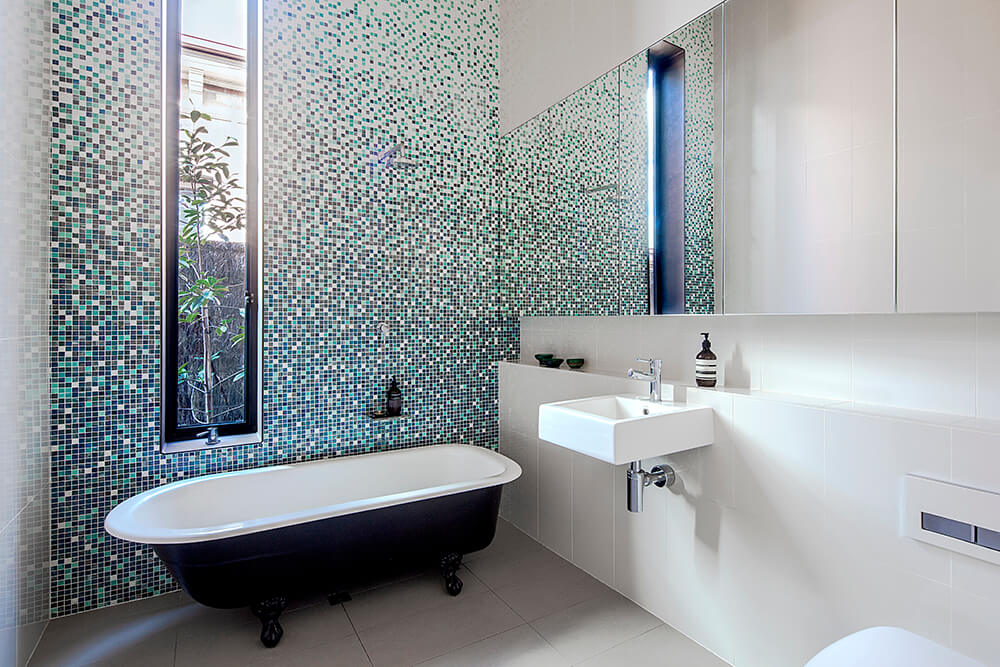 This bathroom features a very enchanting tiles wall near the freestanding tub. The floating vessel sink looks absolutely stunning as well.