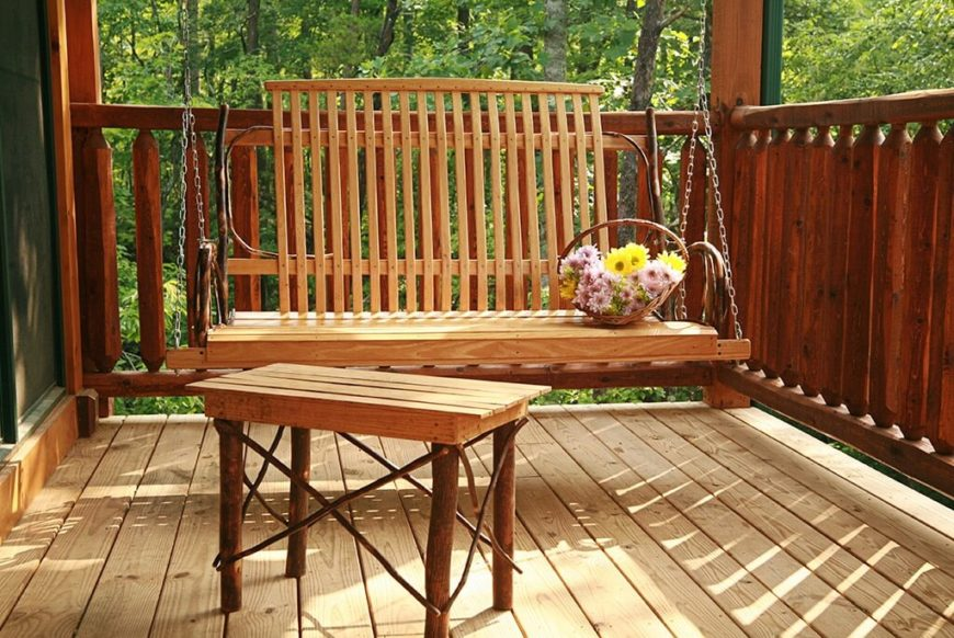 Rustic and charming wooden porch swing with a matching coffee table.
