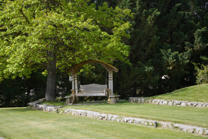 Putting a yard swing out in a shady area is a great way to create an escape. This swing is isolated in the shade of a large tree. A great way to enjoy nature is swaying back and forth under a shady tree.