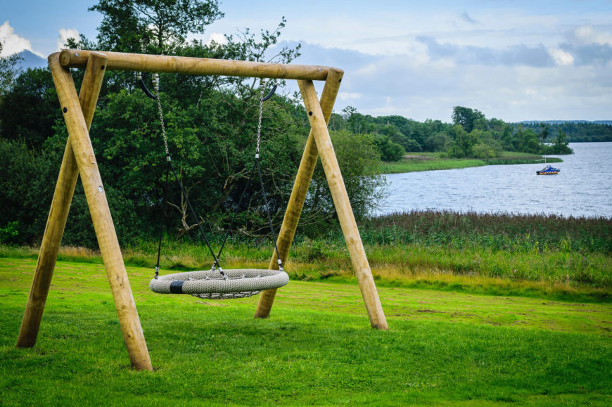 This swing has a circular seat suspended from a wooden frame. The circular seat is great for sitting facing either direction or even laying down.