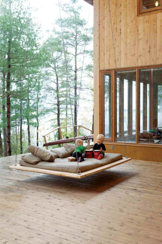 In this picture there is a swing that has been hung from a porch structure. The design of this swing is large and flat, which allows for multiple people to sit or even lay on it as it swings.