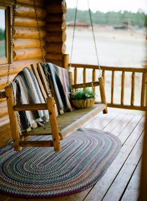 When looking for a porch swing, you will find a large number of styles and designs. A design like the one in this picture, with raw and unfinished wood for a rustic appeal, is great for a cabin look or a space out in the woods.