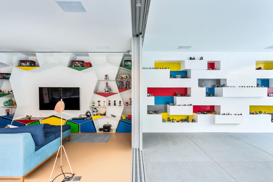 "The living room on this floor features an idiosyncratic, polygonal shelving wall dotted with bright primary colors. To the right is the distinctive ""Lego"" wall, with built-in shelving for hundreds of toys."