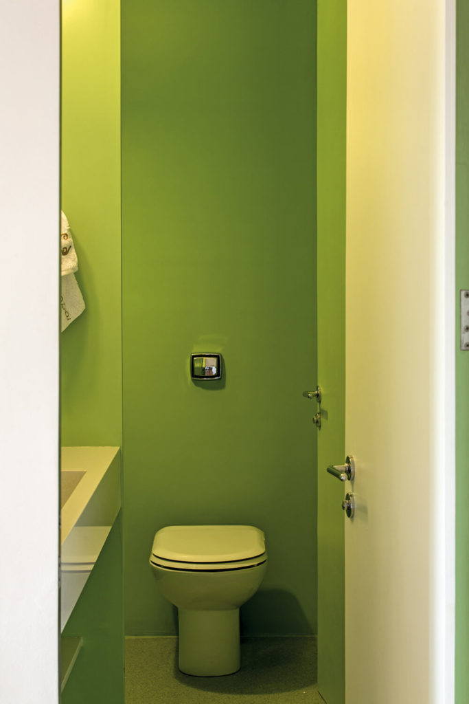 A secondary bathroom stands even further apart with bright lime-green walls and a sleek, minimalist look.
