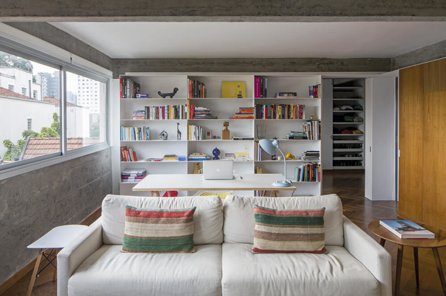 Beyond the living room sofa, we see a white minimalist writing desk with a full size built-in shelving unit at back. The shelving houses much of the color seen in the room, which takes the form of subtle accents and furniture.