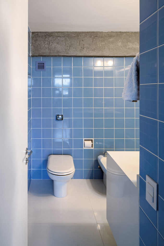 Here's the master bath, standing apart within the apartment with its use of bright blue wall tiles. Even here, the concrete structure makes its presence known.