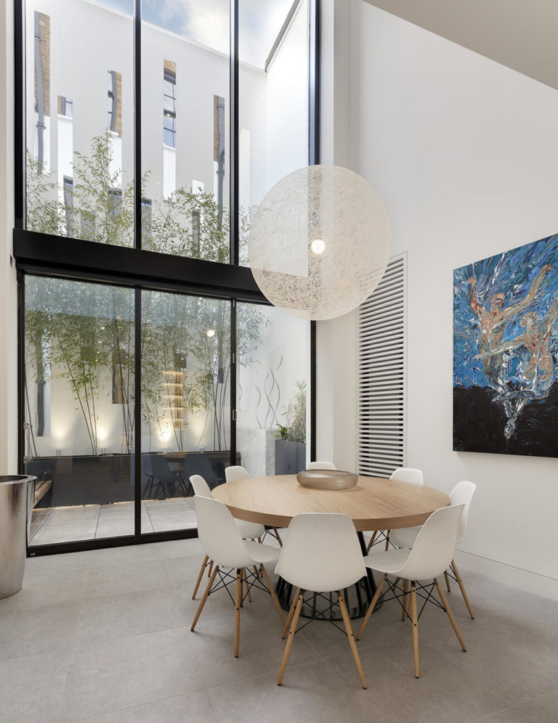 The dining room is wrapped in white and light colors, positively glowing in the natural light provided by the massive, full height windows. A minimalist natural wood table stands surrounded by midcentury modern chairs beneath a large, transparent spherical chandelier.