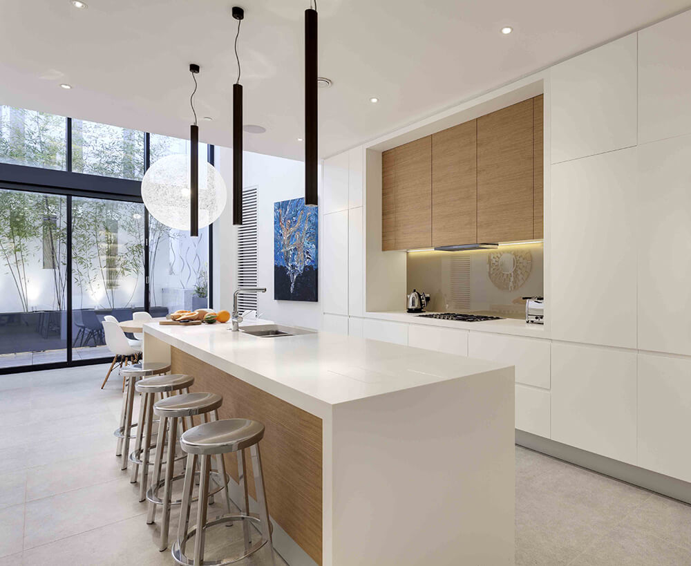 White dine-in kitchen with a breakfast island fitted with a sink and lined with chrome bar stools. It has a wooden vent hood fixed to the glossy backsplash tiles in between sleek cabinetry.