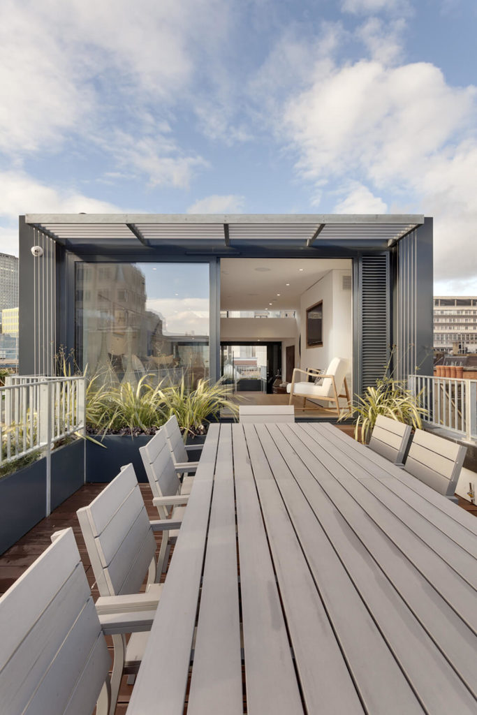In the light of day, we can see hints of the expansive views available to residents of this home, whether inside behind large windows or outdoors on the rooftop terrace.