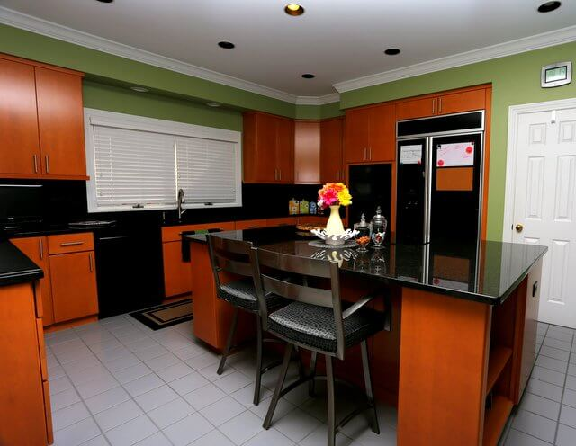 This black granite looks smooth and pure, and goes well with the black appliances. The rich red wooden cabinets add stunning contrast.