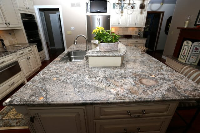 The circular spots and rich veining of this gray granite looks incredible in this cream kitchen.