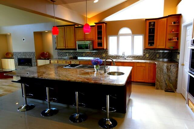 Granite with a copper undertone go well with any cabinets with a slight reddish tone. In yellow lights, these light oak cabinets take on a warm red glow.