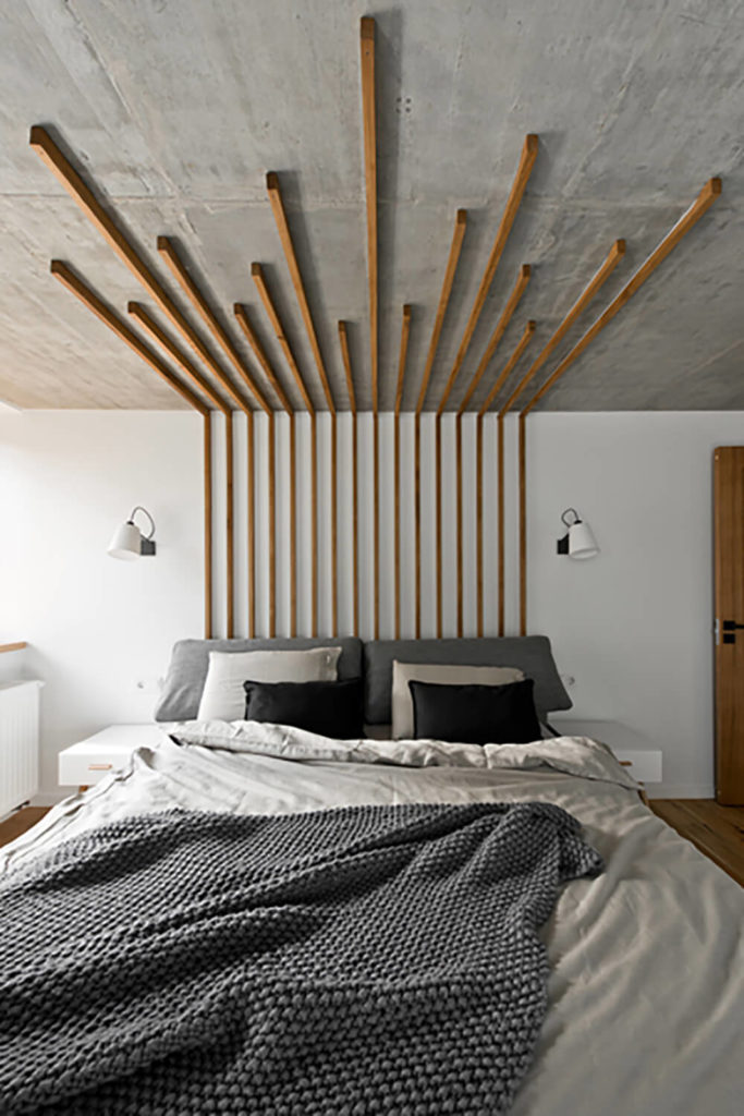 The master bedroom is accented with another unique instance of thin natural wood slats, extending from a pseudo-headboard design across the ceiling. This wraps the entire room into a practical work of art.