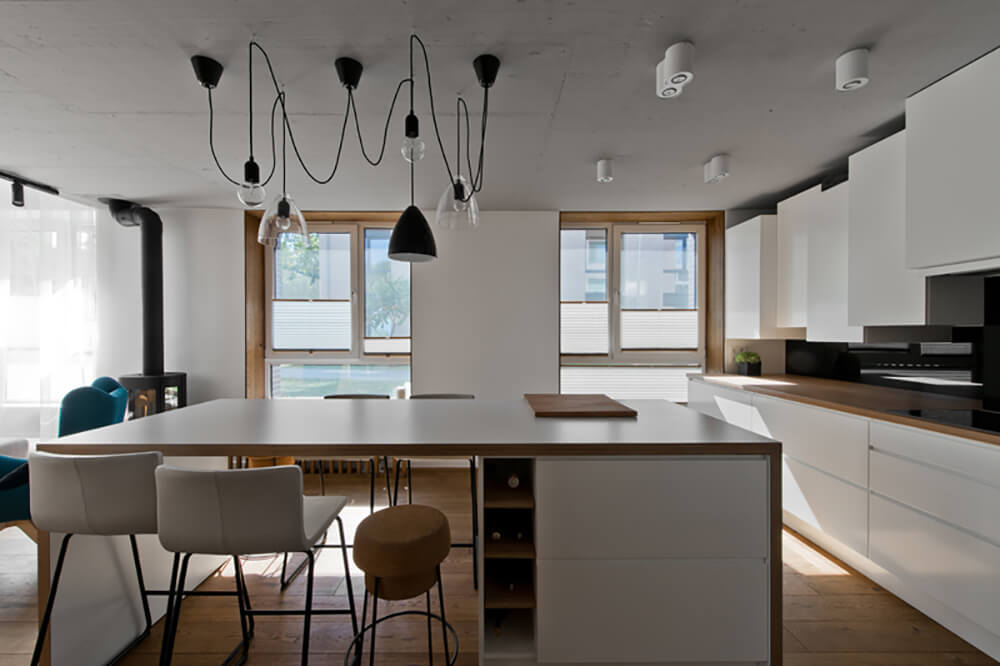 A modish Scandinavian kitchen with a glamorous set of ceiling lights. The hardwood flooring matches the countertops on both kitchen counters and center island.