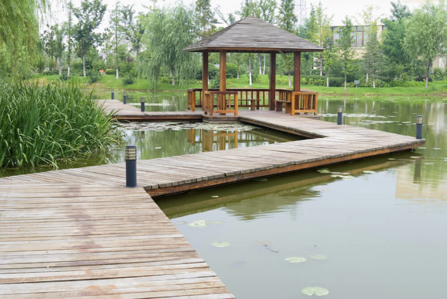 Pavilions are not always on land. A small pavilion out on a deck is perfect. A few benches under the pavilion provide seating to the area so many people can go out and sit in the middle of the small lake.