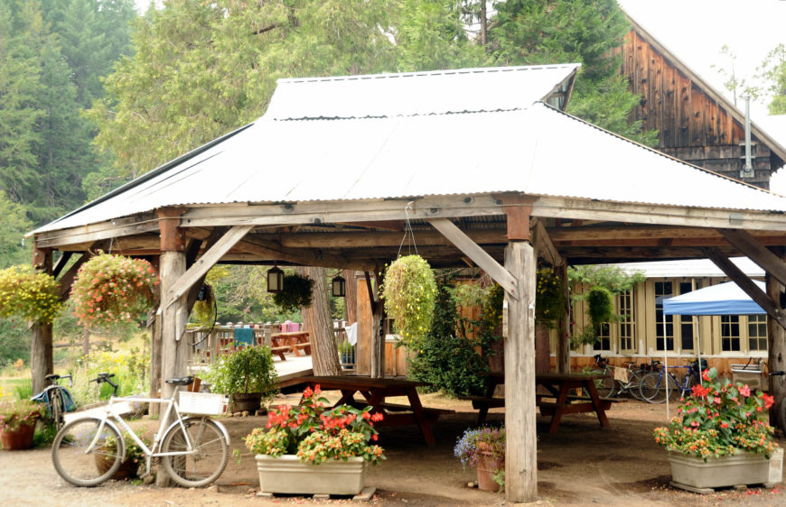 Here is a rustic style pavilion with worn and natural wood beams. Two picnic benches sit under the pavilion ready for a gathering. This natural, raw look provides an antiquity aesthetic that is perfect for the setting. Dirt paths and dusty palettes are at home here.