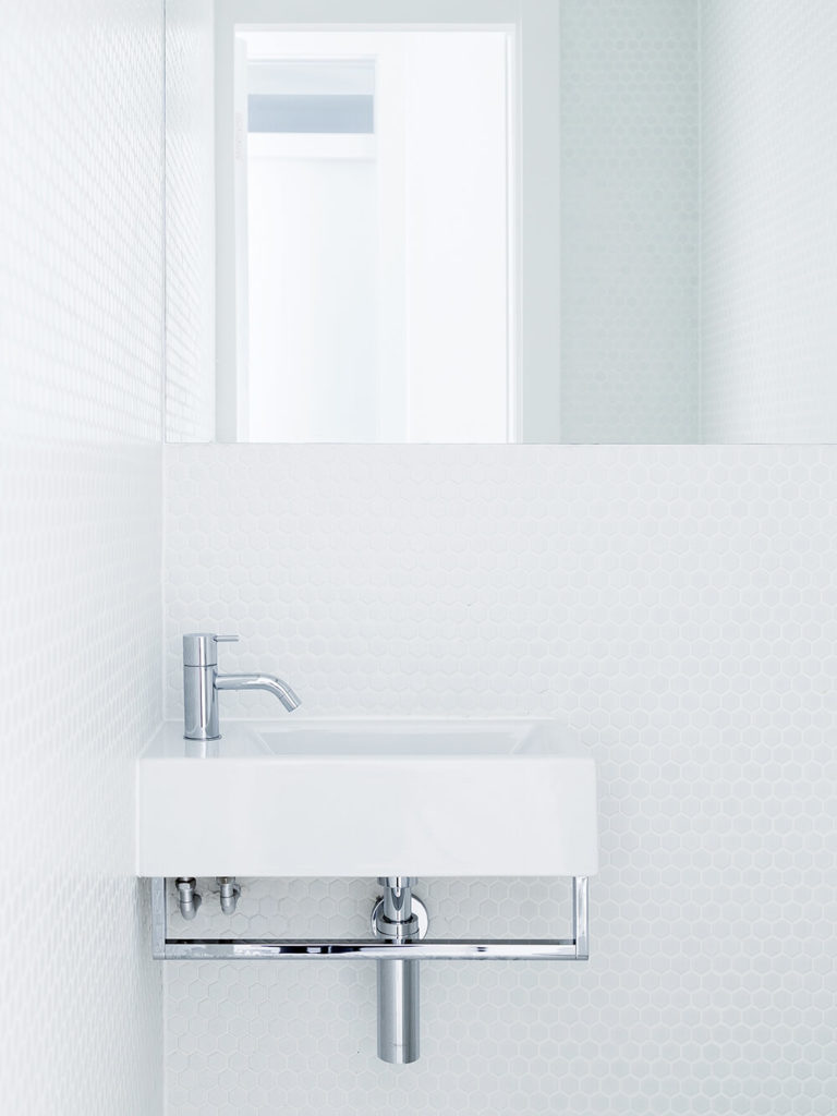 The bathroom boasts a simple, minimalist floating vanity in white and chrome, set against a honeycomb textured white wall.