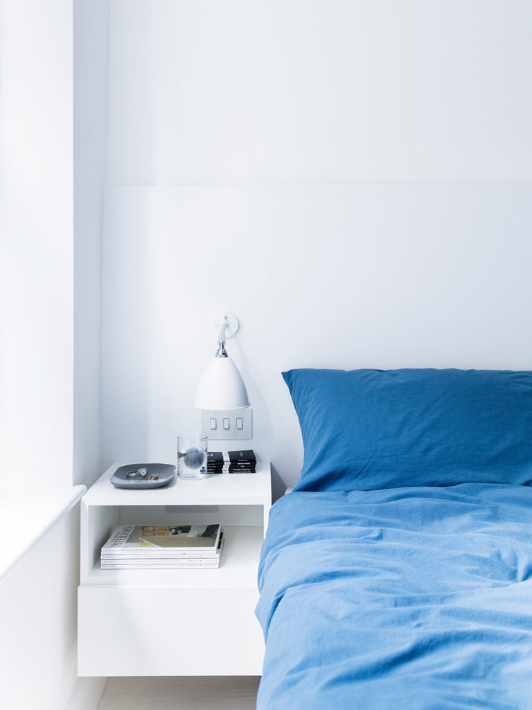 The master bedroom cedes its only instance of color to the bold blue bedspread, with a floating white bedside table mounted on the wall nearby. Large windows afford maximum passive lighting.