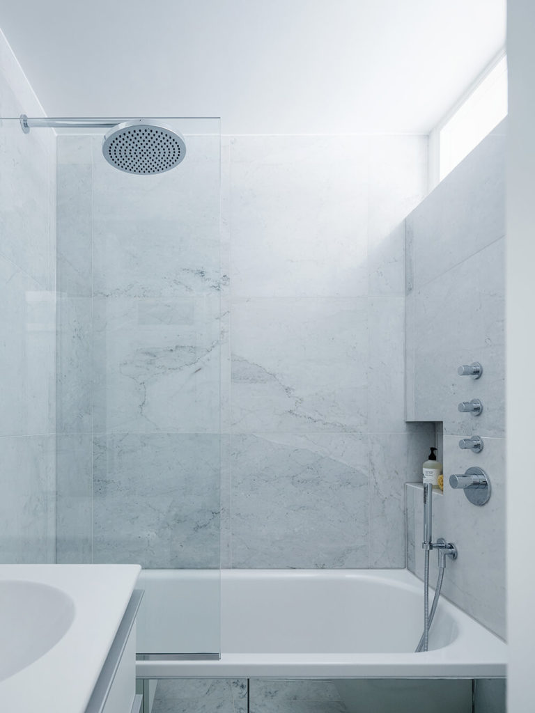 The master bath is awash in white marble, adding a hearty textural element to the white minimalist look. A large soaking tub is framed in glass, while a slim upper window offers some sunlight to the room.