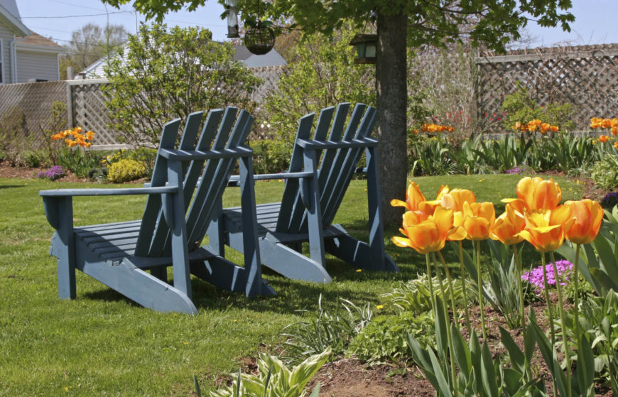 Here is a great pair of Adirondack chairs resting under a tree near a beautiful flower garden. Placing these laid back chairs under a shady spot makes your relaxation destination as comfortable as possible.