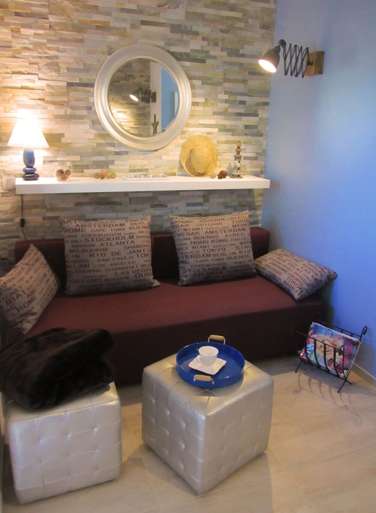 The layered stone on the wall and the blue on another allow the rooms to flow together. A shelf above the sofa allows for a lamp without taking up valuable floor space. Cube ottomans serve as coffee tables and as extra seating.