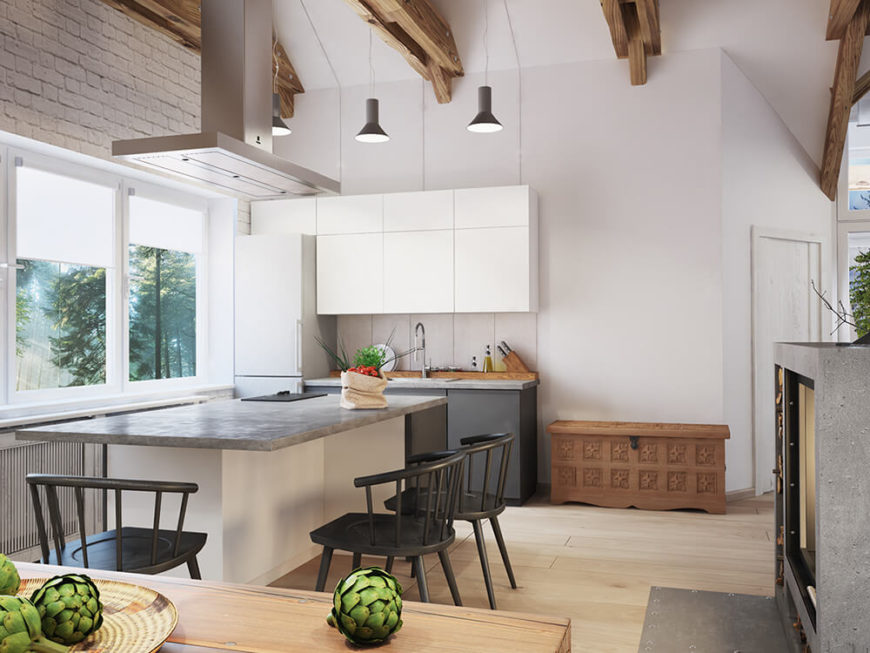 The minimalist cabinetry and cool stone countertops help downplay the presence of the kitchen within the larger space, but the large island defines it with plentiful space even for a trio of diners.