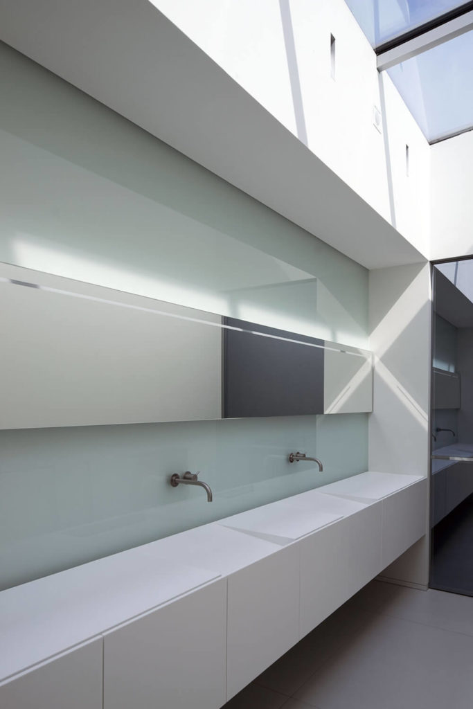 The bathroom is as sleek and minimalist as anywhere else within the home. A lengthy vanity features two stealthy sinks and a glass backsplash, with skylights above providing natural light.