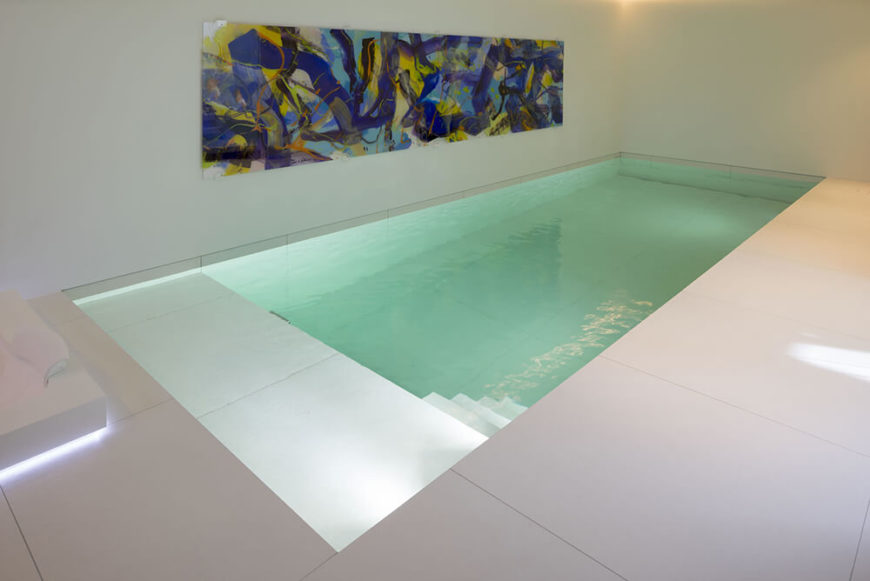 This unique pool design is of-a-piece with the angular, sleek nature of the home itself, fitted directly into the floor without a discernible border. A massive, colorful work of art adorns the wall, bringing a blast of texture to the area.