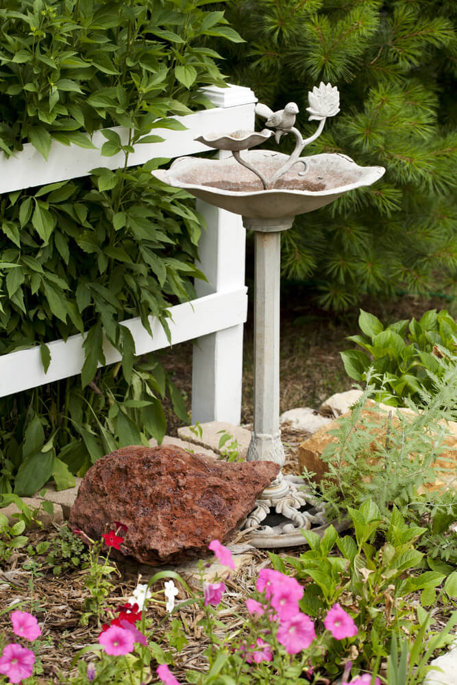Pictured here is a metal bird bath painted white with a little white metal bird perched upon it. No bird will feel lonely swimming here with this permanent resident hanging out nearby.