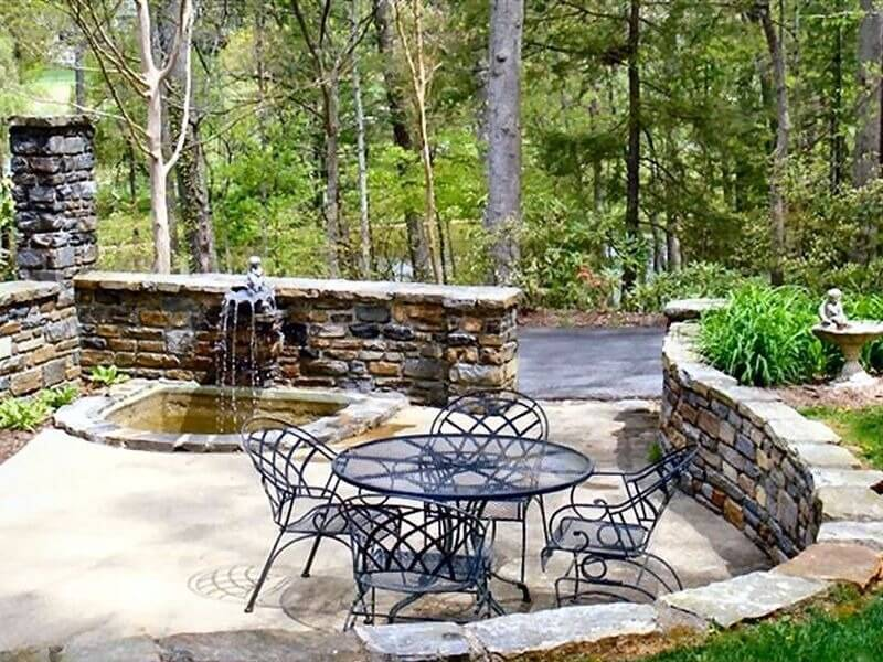 Stone fountains and bird baths fit well in walls and other stone structures. This fountain and bird bath is built into this stone half wall, making this bath a cohesive part of this area's design.