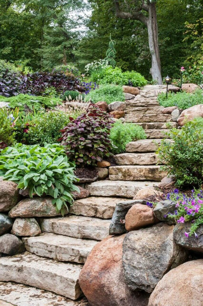 If you have a stone walkway or steps you may consider letting some of your perennial bushes and flowers grow wild alongside these areas. It helps increase the rustic and naturalistic appeal of the area.