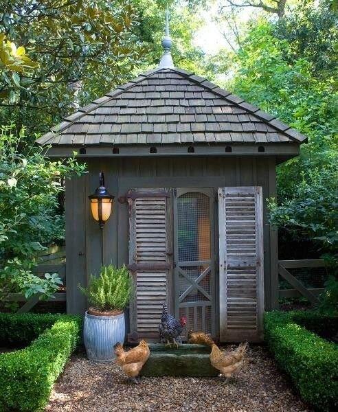We cannot resist an adorably constructed chicken coop with quaint rustic styling. This large structure features a handsome black metal sconce and is even flanked by miniature hedge rows.