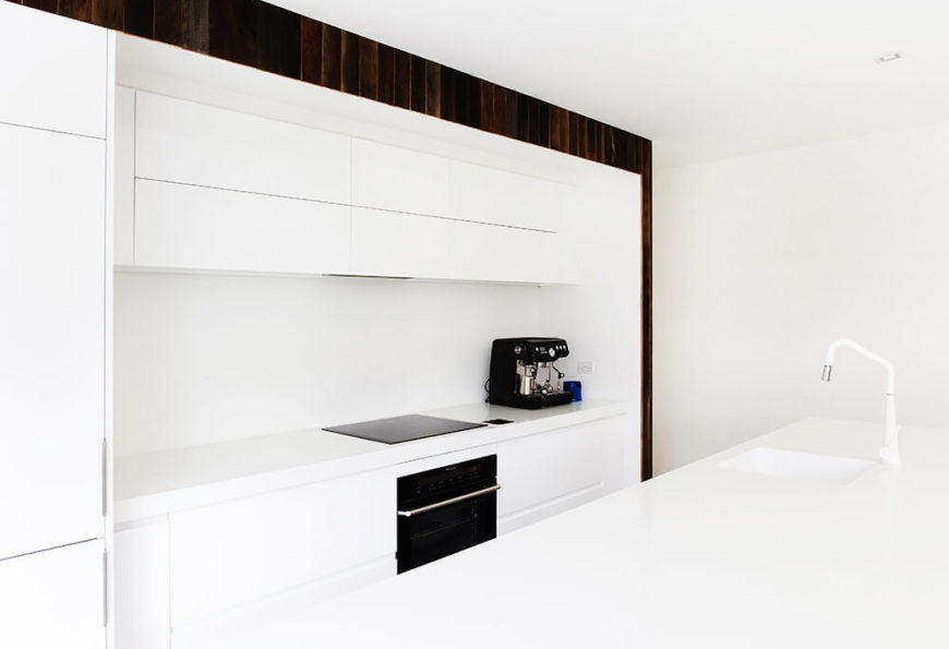 The kitchen is defined by its large island and all-white coloring, with sleek hardware-less cabinetry and minimalist appliances. A small border of natural wood panels frames the space.