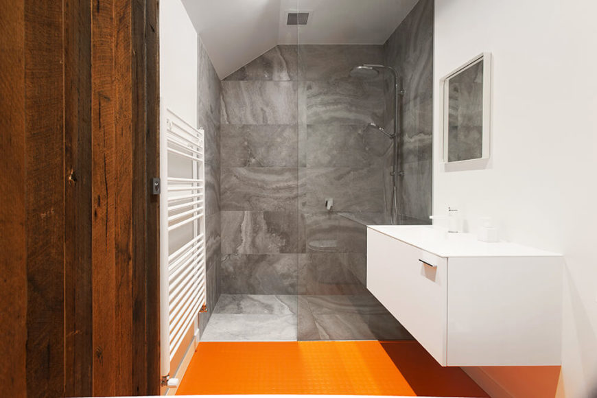 The master bathroom sports a bold orange floor in high contrast with the rest of the home's muted palette. This is complemented by a floating white vanity and walk-in shower wrapped in marble.