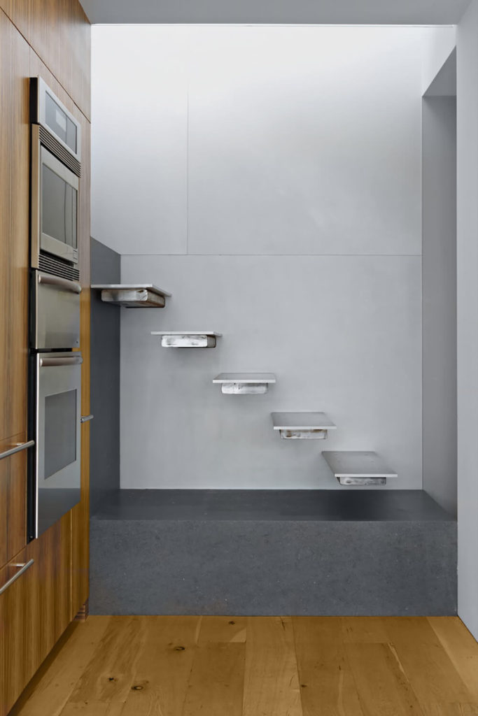A floating staircase leads to the second floor, keeping the modern, minimalist flow of the apartment in mind. These stairs appear just off of the kitchen area.