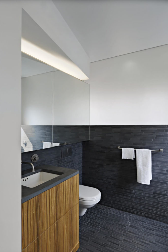 The same wood continues into the bathroom, adding a bit of warmth back into the otherwise starkly contrasting white walls and charcoal tiles.