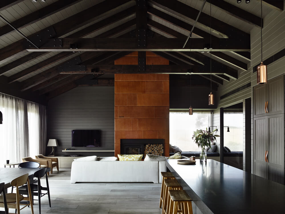 A contemporary great room with dark finished walls and a vaulted ceiling with beams. The fireplace looks perfect together with the dark shade surrounding the space.