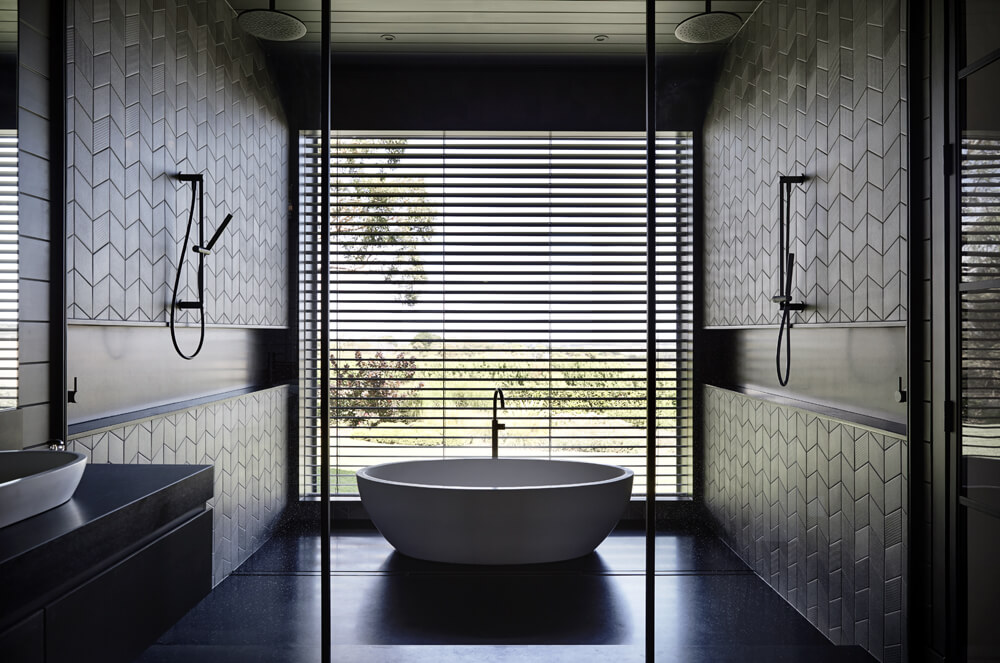 This gloomy bathroom with a freestanding tub and an open shower looks elegant due to the dark finish of the walls and floors.